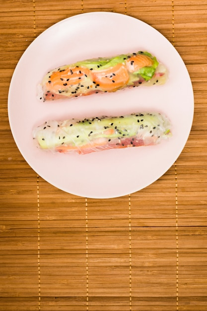 Vista elevada, de, asiático, rolos primaverais, com, peixe salmão, e, vegetal, ligado, prato branco, sobre, placemat Foto gratuita