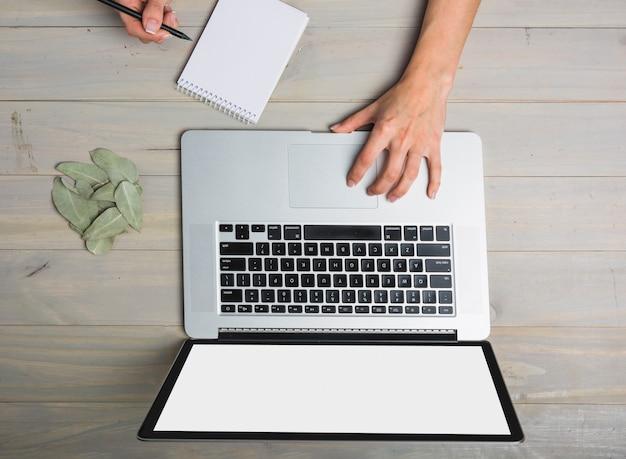 Vista elevada, de, businessperson, usando computador portátil, enquanto, escrita, ligado, notepad Foto gratuita