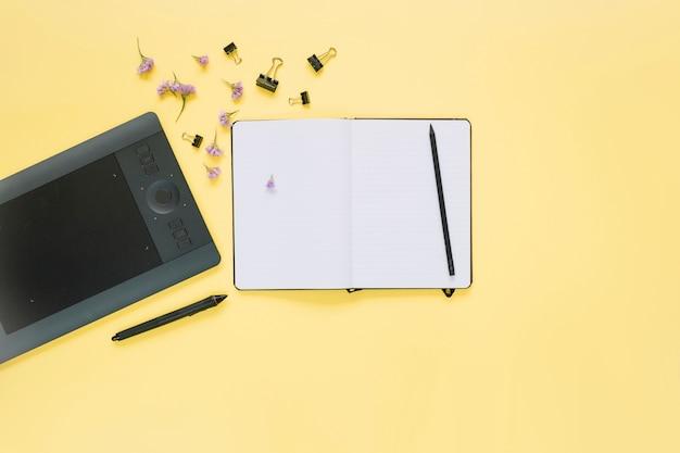 Vista elevada, de, caderno aberto, e, gráfico, tablete digital, ligado, amarela, superfície Foto gratuita
