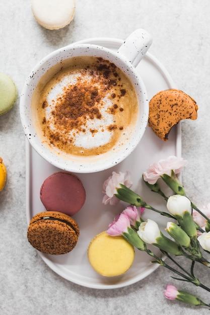 Vista elevada, de, café, e, macaroons, com, grupo, de, flores frescas Foto gratuita