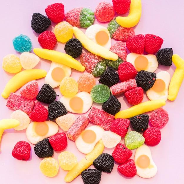 Vista elevada, de, colorido, geléia, e, gomoso, açúcar, bala doce, ligado, fundo cor-de-rosa Foto gratuita