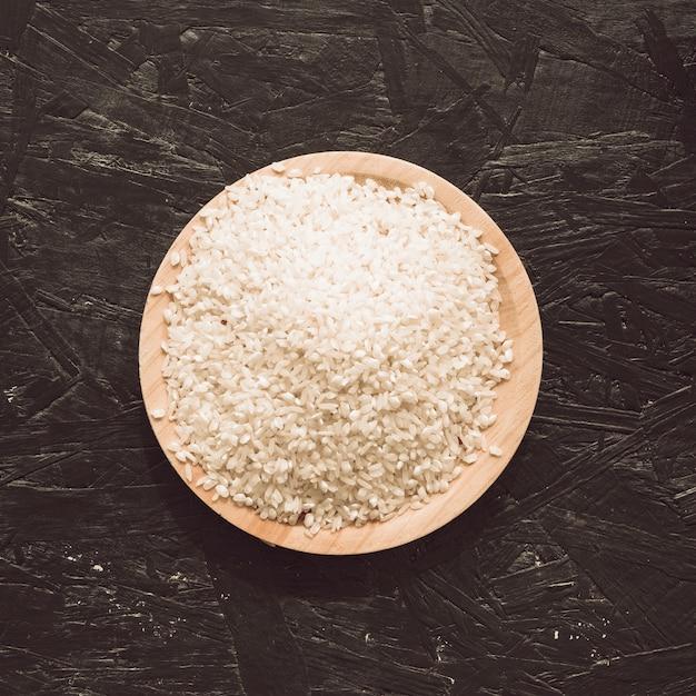 Vista elevada, de, cru, arroz, grãos, em, tigela, ligado, áspero, cinzento, fundo Foto gratuita
