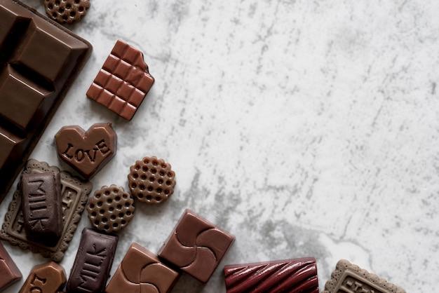 Vista elevada de deliciosas barras de chocolate contra pano de fundo texturizado branco Foto gratuita