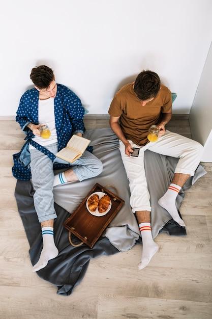 Vista elevada, de, dois, homem, leitura, livros, segurando, suco jarro Foto gratuita