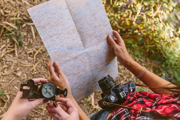 Vista elevada, de, duas mulheres, segurando, compasso, e, mapa Foto gratuita