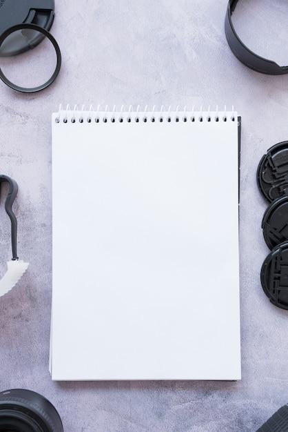 Vista elevada, de, em branco, aberta, espiral, notepad, com, câmera, acessórios, ligado, concreto, fundo Foto gratuita