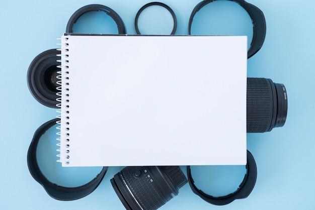 Vista elevada, de, em branco, espiral, notepad, sobre, câmera, acessórios, ligado, experiência azul Foto gratuita
