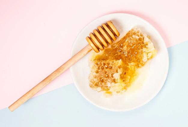 Vista elevada, de, favo mel, e, madeira, mel, dipper, em, branca, prato Foto gratuita