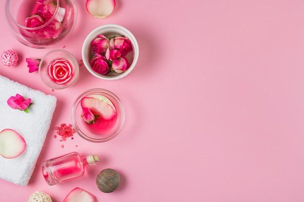 Vista elevada de flores; óleo essencial; pedras de spa e toalha no fundo rosa Foto gratuita