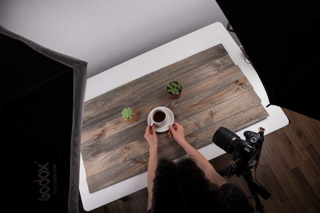 Vista elevada, de, fotógrafo, organizando, xícara chá, para, tiro, em, estúdio Foto gratuita