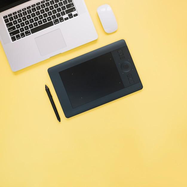 Vista elevada, de, gráfico, tablete digital, e, laptop, ligado, experiência amarela Foto gratuita
