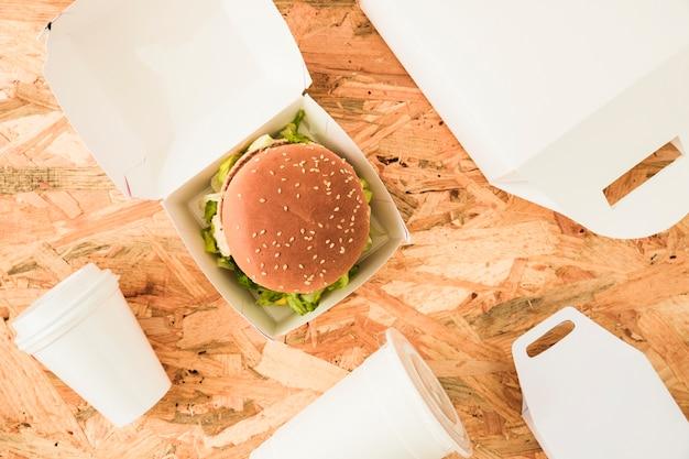 Vista elevada de hambúrguer com copos de eliminação e pacotes em fundo de madeira Foto gratuita