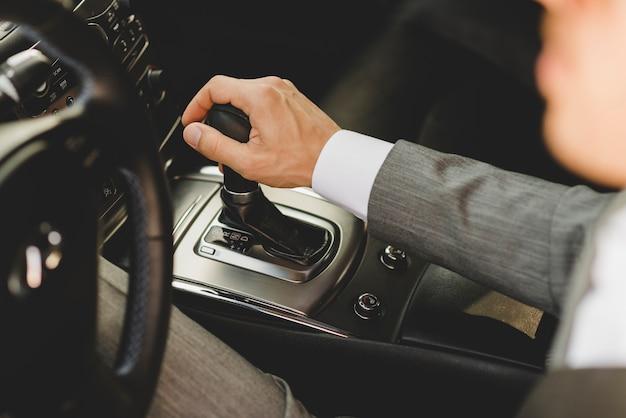 Vista elevada, de, homem negócios, dirigindo, carro, em movimento, transmissão, engrenagem mudança Foto gratuita