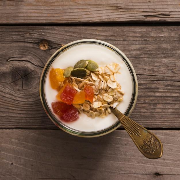 Vista elevada de iogurte com muesli, sementes de abóbora e frutas na mesa de madeira rústica Foto gratuita