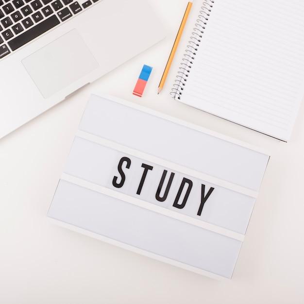Vista elevada, de, laptop, com, stationeries, e, estudo, texto Foto gratuita