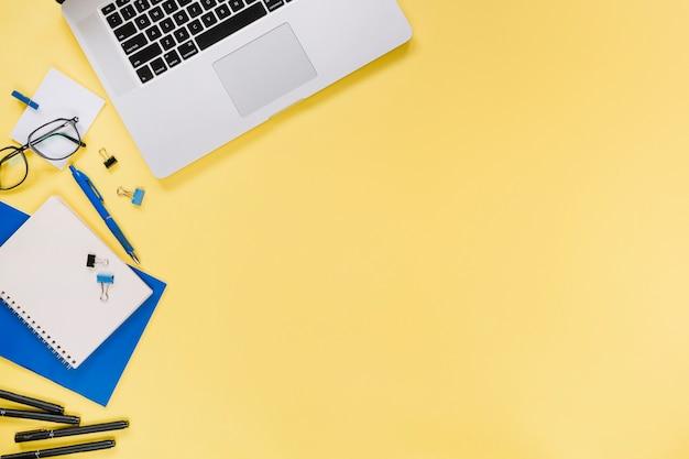 Vista elevada, de, laptop, e, stationeries, ligado, amarela, fundo Foto gratuita