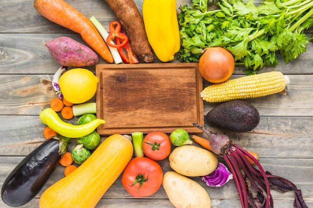 Vista elevada, de, legumes crus, cercar, tábua madeira, tábua cortante Foto gratuita