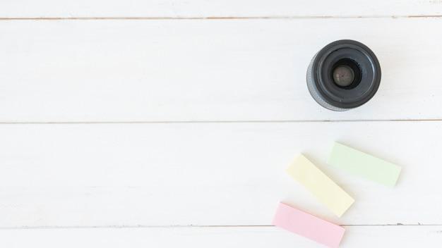 Vista elevada, de, lente câmera moderna, com, colorido, notas pegajosas, ligado, tabela madeira Foto gratuita