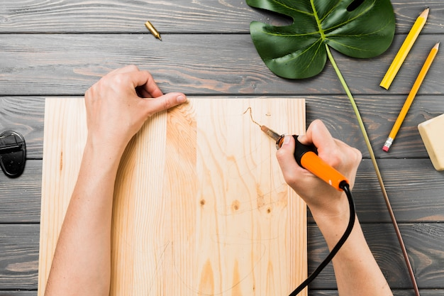 Vista elevada, de, mão, esculpa, difícil, tábua madeira, escrivaninha Foto gratuita