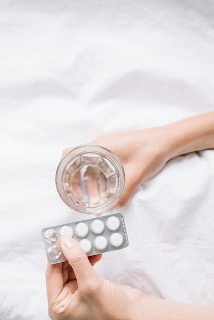 Vista elevada, de, mão mulher, segurando, copo água, e, pílulas Foto gratuita
