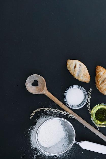 Vista elevada de massa folhada; farinha; açúcar; óleo; grãos e utensílios na superfície preta Foto gratuita
