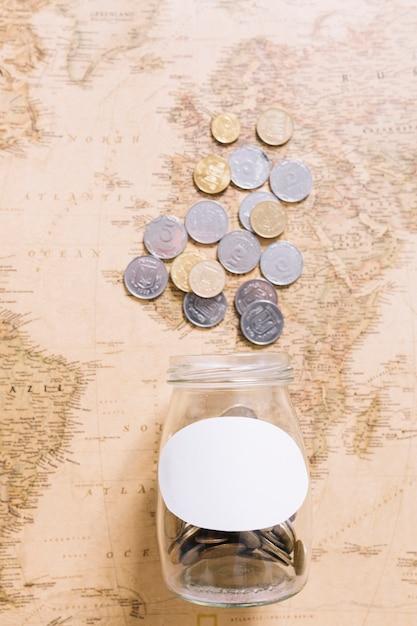 Vista elevada, de, moedas, sobre, a, jarro aberto, ligado, mapa mundial Foto gratuita