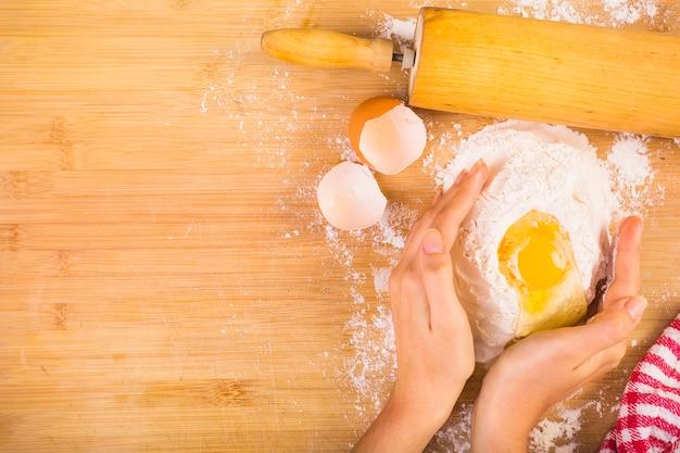 Vista elevada, de, mulher, mão, misturando farinha, com, ovo Foto gratuita