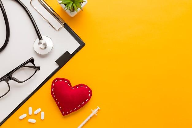 Vista elevada de óculos; comprimido; injeção; forma de coração costurada; planta suculenta; estetoscópio sobre fundo amarelo Foto gratuita