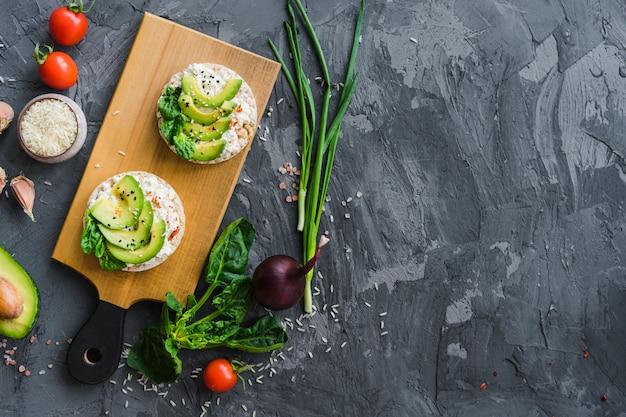 Vista elevada, de, orgânica, legumes, com, saboroso, bolo arroz, refeição, sobre, cinzento, áspero, concreto, fundo Foto gratuita
