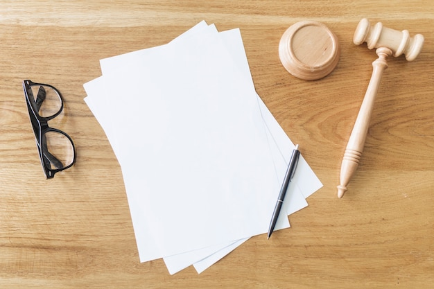 Vista elevada de papéis em branco; óculos; caneta e martelo de madeira na mesa na sala de audiências Foto gratuita