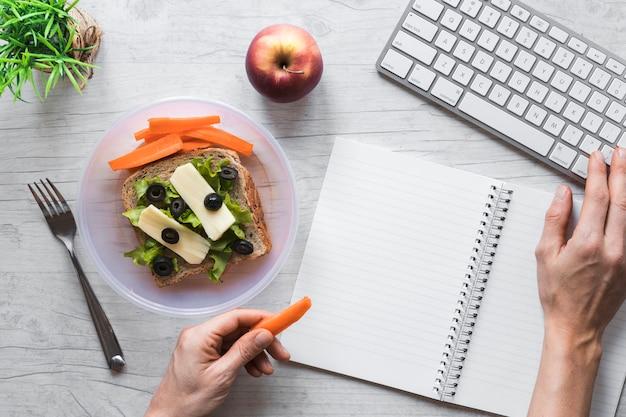 Vista elevada, de, pessoa, mão, segurando, alimento saudável, enquanto, trabalhando, ligado, teclado Foto gratuita