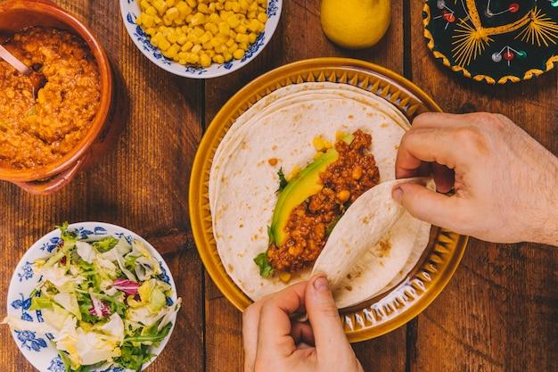 Vista elevada, de, pessoas, mão, preparar, envolver, tacos carne, para, café da manhã Foto gratuita