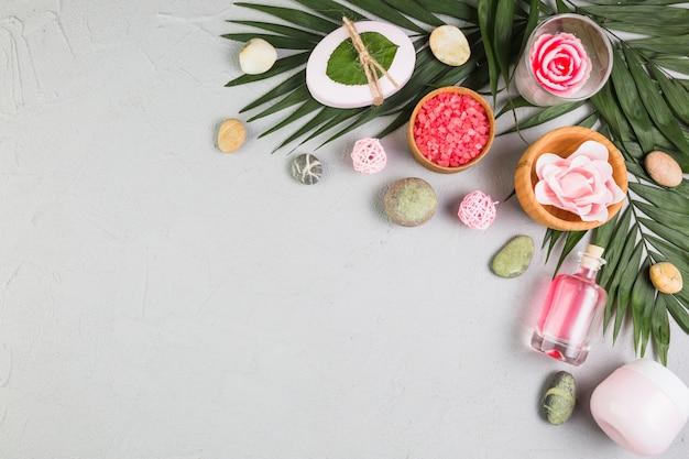 Vista elevada de sabão; pedras de spa; sai; creme hidratante; óleo e flores na superfície cinza Foto gratuita