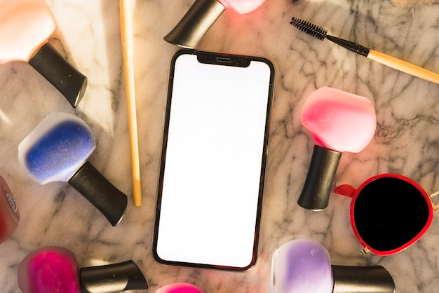 Vista elevada de smartphone com esmalte colorido e rímel em fundo de mármore Foto gratuita