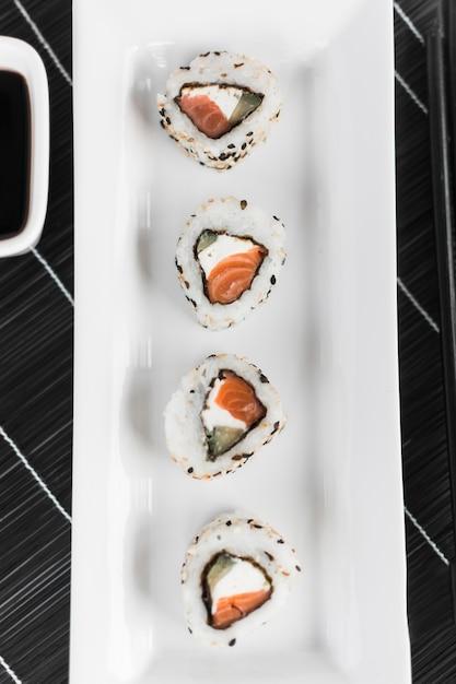 Vista elevada, de, sushi, organizado, branco, bandeja, sobre, a, lugar, tapete Foto gratuita