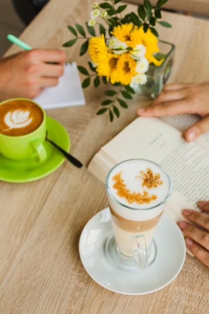 Vista elevada, de, xícara café latte, perto, pessoas, estudar, em, caf� Foto gratuita