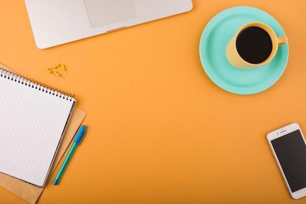 Vista elevada do café preto; smartphone; caneta; pinos de pressão; laptop e bloco de notas em pano de fundo laranja Foto gratuita