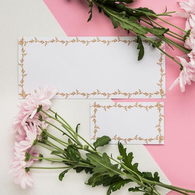 Vista elevada do cartão em branco com flores frescas no fundo duplo Foto gratuita