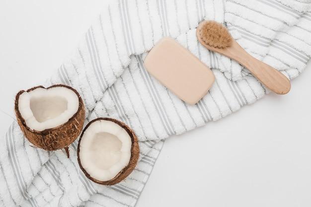 Vista elevada do coco cortado ao meio; toalha; sabão e escova no pano de fundo branco Foto gratuita