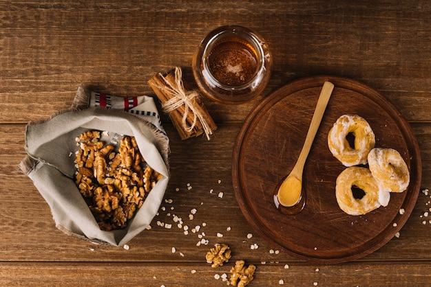 Vista elevada do mel; noz; especiarias e donuts na superfície de madeira Foto gratuita
