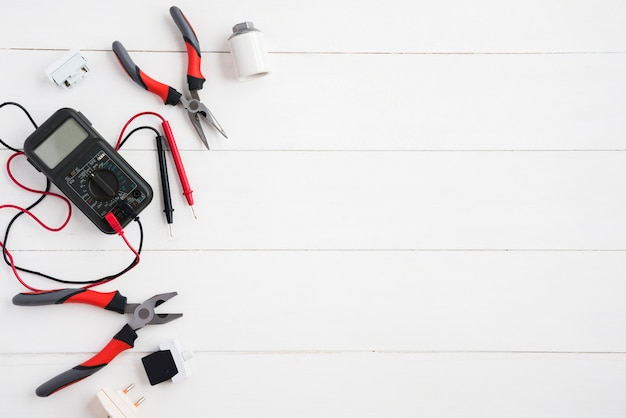 Vista elevada do multímetro digital e equipamento elétrico na mesa de madeira branca Foto Premium