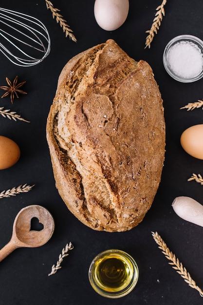 Vista elevada do pão delicioso com vários ingredientes e utensílios de cozimento na superfície preta Foto gratuita