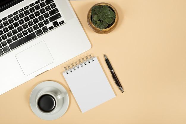 Vista elevada do portátil; xícara de café; caneta; e o bloco de notas em espiral sobre fundo bege Foto gratuita
