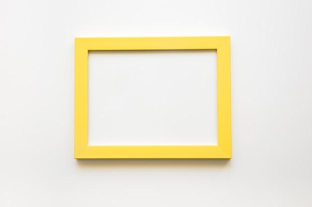 Vista elevada do quadro amarelo em branco sobre fundo branco Foto gratuita
