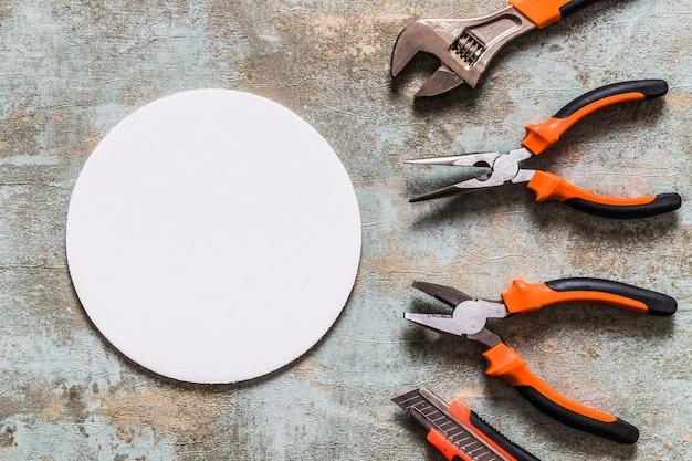 Vista elevada do quadro circular branco, além de várias ferramentas de trabalho Foto gratuita