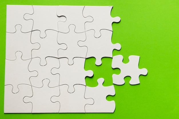 Vista elevada do quebra-cabeça de papelão no fundo verde Foto gratuita