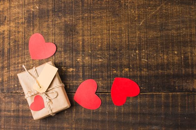 Vista elevada dos corações; caixa de presente e tag no painel de textura Foto gratuita