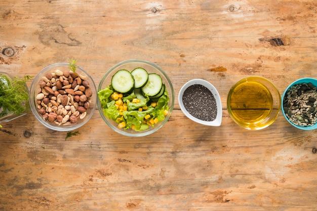 Vista elevada dos dryfruits; óleo; sementes de chia e ingredientes dispostos em uma linha na mesa de madeira Foto gratuita