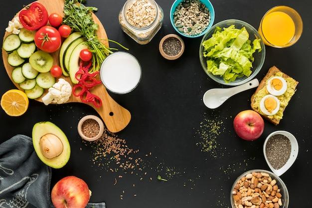 Vista elevada dos ingredientes; dryfruits e legumes em fundo preto Foto gratuita