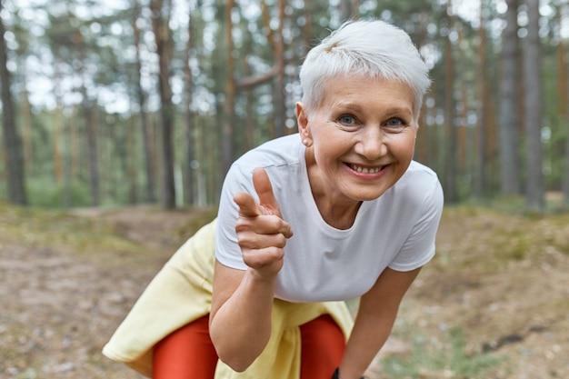 Vista externa de uma mulher aposentada alegre e enérgica em roupas esportivas, inclinando-se para a frente, sorrindo e apontando o dedo dianteiro Foto gratuita